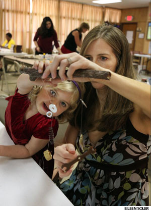 Christina Gray and her daughter Sarah, 4, put their heads together at Trinity to create a wind chime during an intergenerational, highly interactive worship service that provides faith formation. The chime's components were selected to symbolize Christian beliefs.