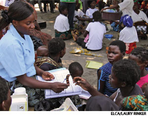 A nurse in Malawi teaches families about the schedule for taking malaria medicine.