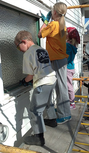 Photo by Lori Prater Holden Kohlmeyer and Mia and Anya Prater, members of Atonement Lutheran Church, Boulder, Colo., prep a house for painting in Green River, Utah, while on a mission trip. They also replaced leaking windowpanes on the house as part of Atonement's partnership with the Epicenter's Fix It First program.