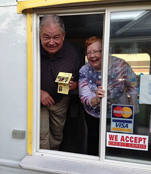 Below, Don Skadow and Sheryl Grimstad serve up free ice cream from the rented truck's rear window.