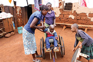 Calvin, a child with disabilities, receives an in-home medical screening from Building a Caring Community (BCC) administrators in a remote part of the Rau KDC area in Tanzania.