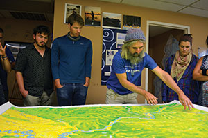 Ricky Taylor John Ruskey (second from right) of Quapaw Canoe Co. shows Augsburg students his maps of their route on the Lower Mississippi.