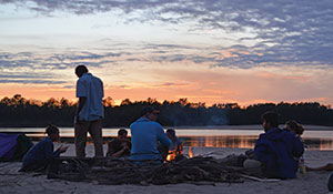 Ricky Taylor River Semester students converse around a fire as they set up camp for a night on the shore of the Mississippi River.