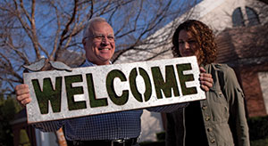 Dave Nagel Jim Harter, with Carmen Pease, holds up the sign for the new welcome center at Messiah.