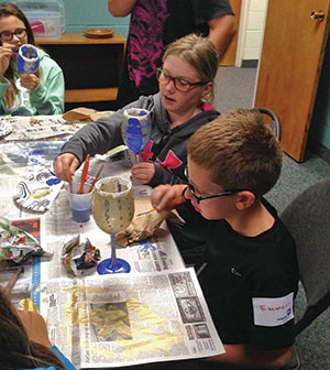 "COURTESY OF METIGOSHE MINISTRIES Ava Lee (left) and Emmett Kersten from Zion Lutheran Church, Berthold, N.D., paint chalices at a first communion-themed ""Metigoshe in Motion"" retreat, a ministry of Metigoshe Ministries in Bottineau, N.D."