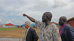 ANDREW STEELE/ELCA Ariik shows Mark Jacobson (left), an ELCAmissionary, and Atem the future site of the Lutheran center and clinic. The center is situated in an area that lacks basic health and education services.