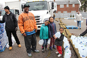 Edward Osborn, a member of Salem Lutheran Church, Flint, Mich., gets help collecting water donated by Holy Trinity Lutheran Church, Livonia, Mich., from Ahmya Miller, 7; Qua'Nyra Page, 10; and Demoni Goddard, 3.