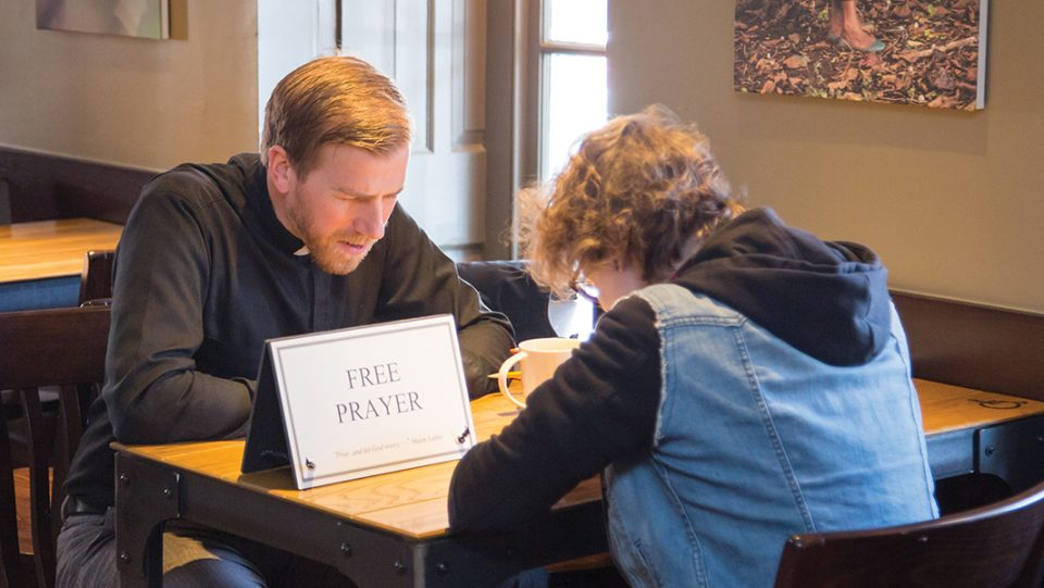 "Every Thursday, Thomas Rusert, a pastor of St. Paul Lutheran Church, Doylestown, Pa., takes a sign that says ""Free prayer"" to a coffee shop to make himself more available to his community. Rusert said someone has taken him up on the offer every week since he started the practice almost a year ago."