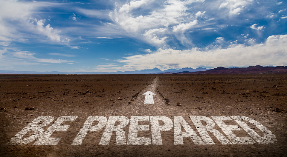 """The words """"be prepared"""" on a desert road under a big, blue sky"""