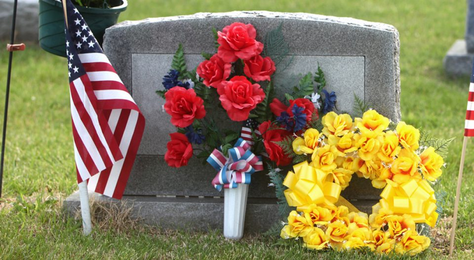 Flags and floral wreaths adorn a gravestone.