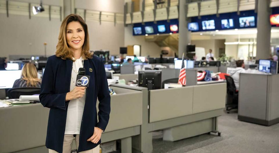 Miriam Ruth Hernandez, news broadcaster, stands in a news station.