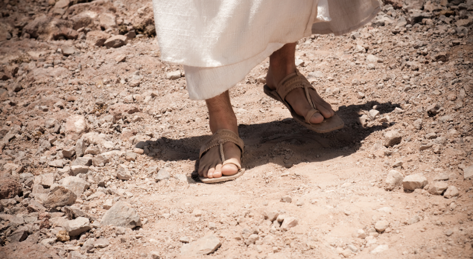 Feet beneath a white robe wearing sandles on a dusty pasth.