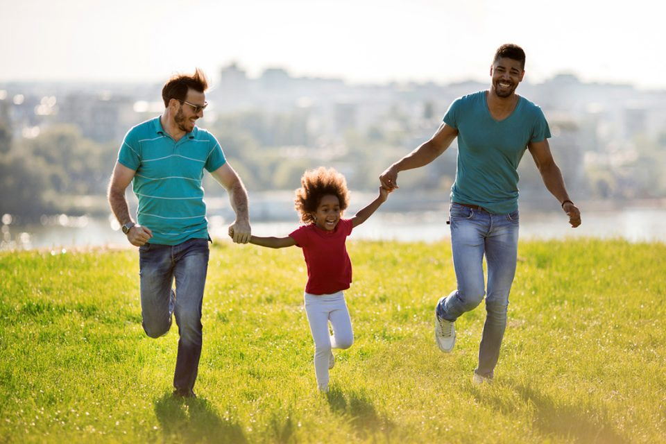 Gay parents holding hands with their adopted African American daughter and laughing while running together in the park.