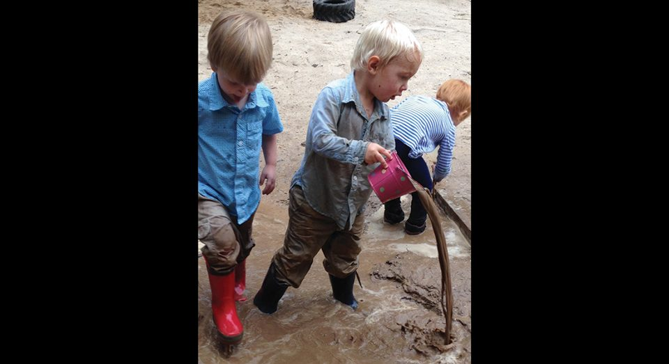 Three preschool students play in messy mud.