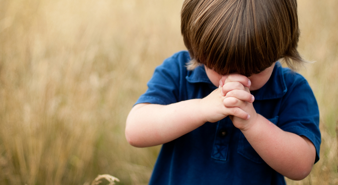 A young boy with hands folded in prayer