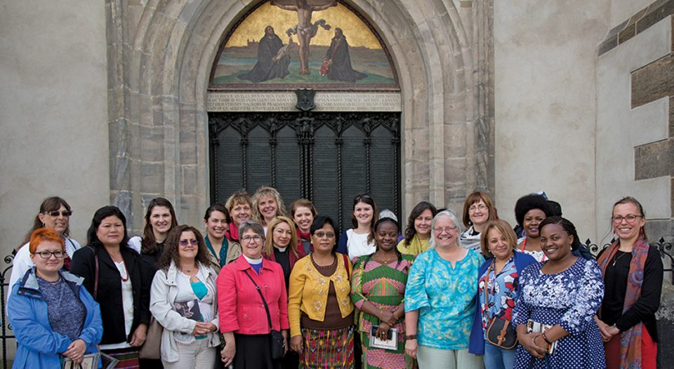 22 women stand in front of the historic All Saints' Church (Castle Church) in Wittenberg, Germany.