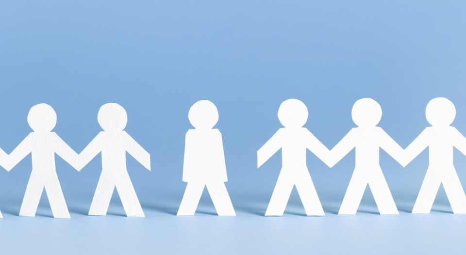 White paper cutout figures holding hands with one excluded on a blue background.