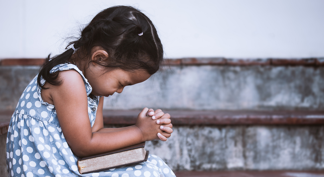 A little girl prays with eyes tightly shut and hands tightly folded.