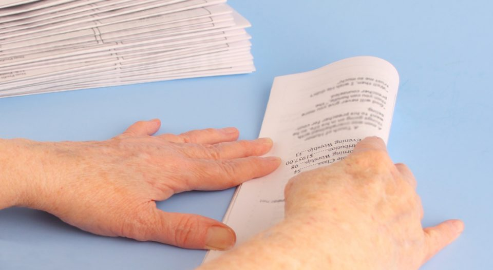 A woman's hands fold church newsletters.