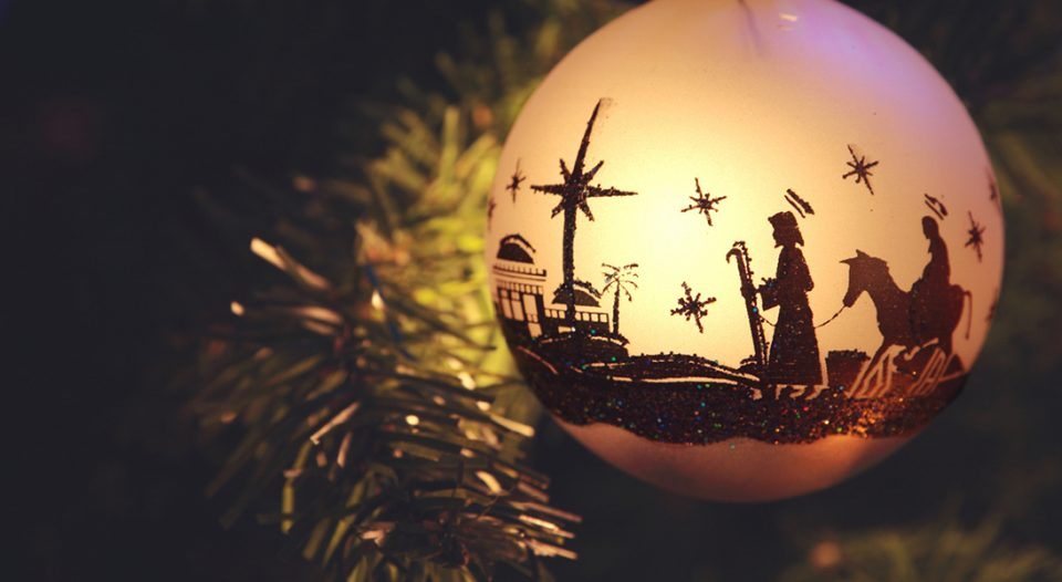 Christmas ornament with silhouette of nativity scene with Mary, Joseph, and Bethlehem. Ornament is hanging from branch of tree.