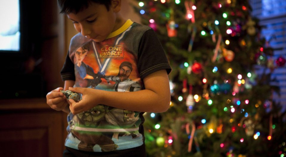 A young boy wearing his Star Wars pajamas and playing with his new Bakugan toy. Christmas tree is lit in the background.