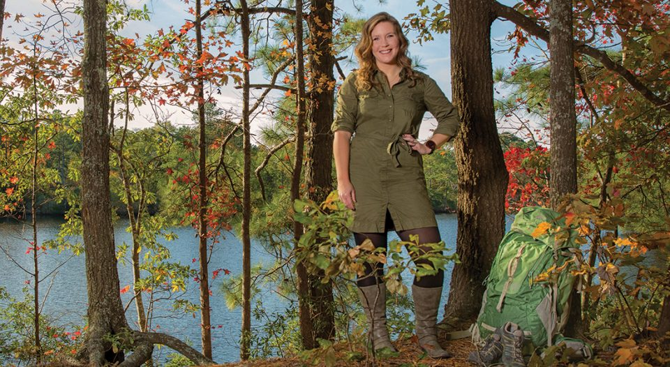 A young woman stands before a lake sourrounded by woods in fall foliage.