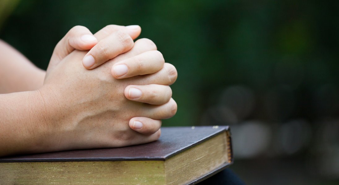 Young hands are folded in prayer on a Bible.