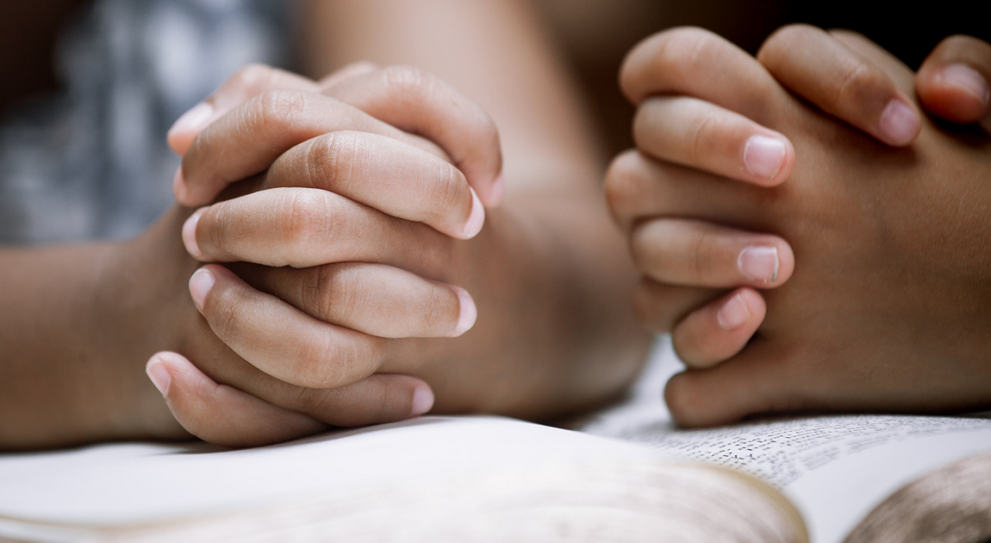 Two pairs of young hands folded in prayer.