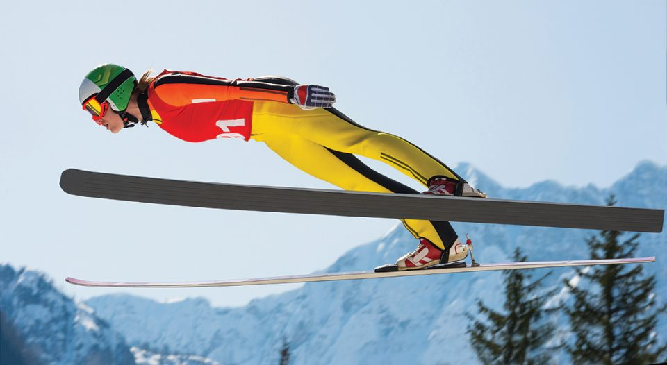 Side view of young female ski jumper during the long ski jump against the sky and mountains.