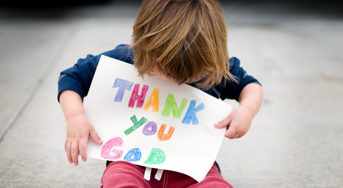 A young child holds a handmade sign that says Thank you God