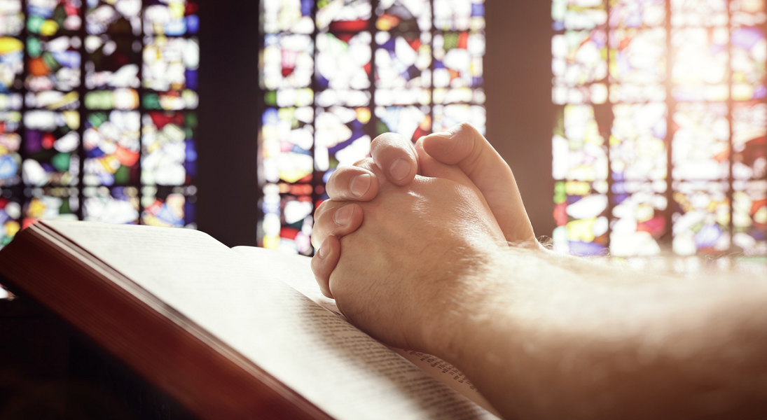 Hands folded in prayer on a Bible against a stained-glass background