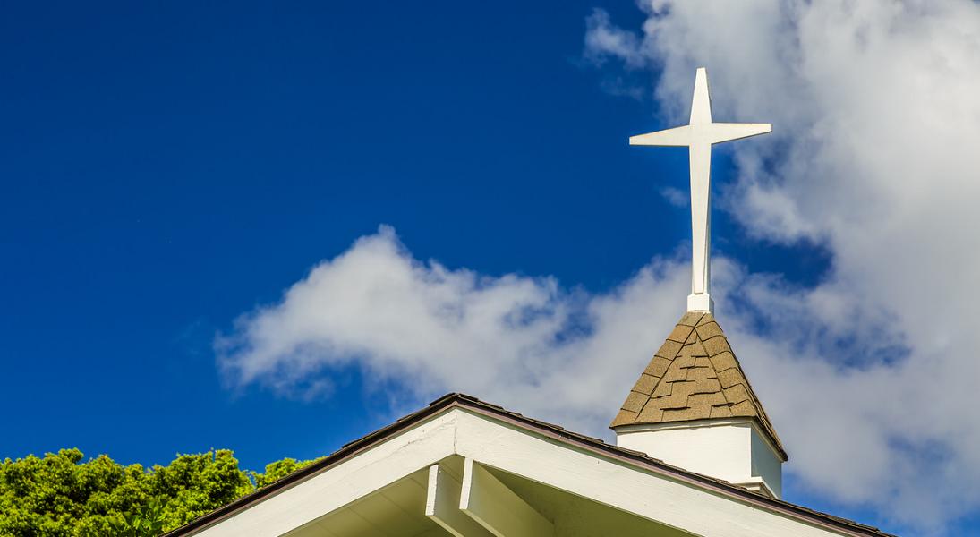 A white cross atop a church against a blue sky.