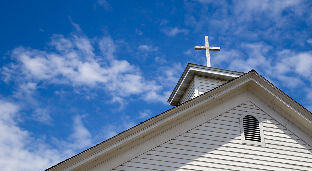 Looking up at a cross atop a white church against a blue sky.