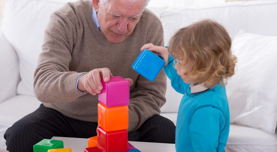 Grandpa and child playing with color cubes.