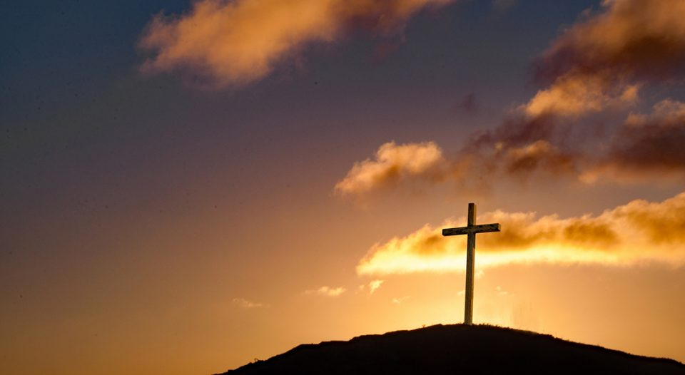 Cross on hilltop with setting sun behind the crucifix.