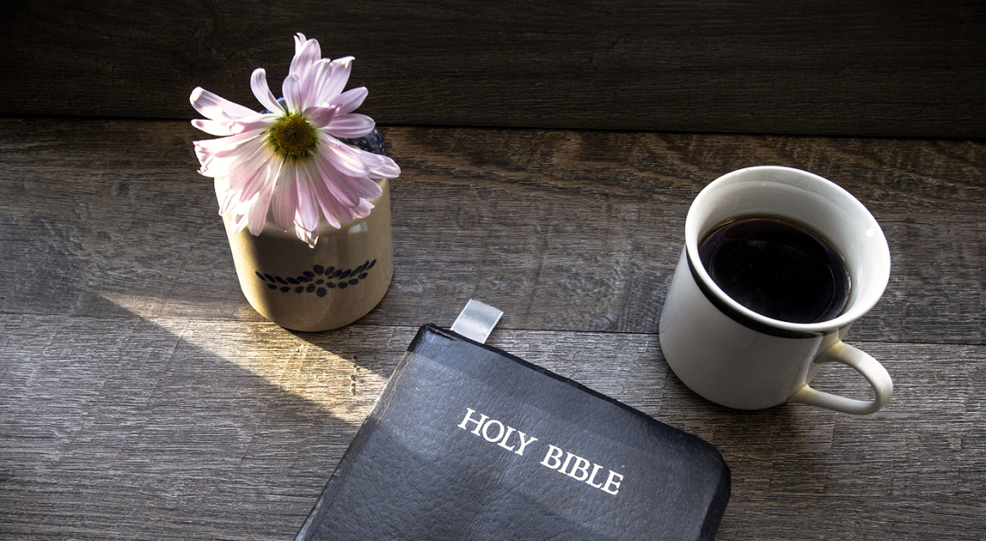 A single flower in a jar, a full coffee mug and a closed Bible on a wooden table top