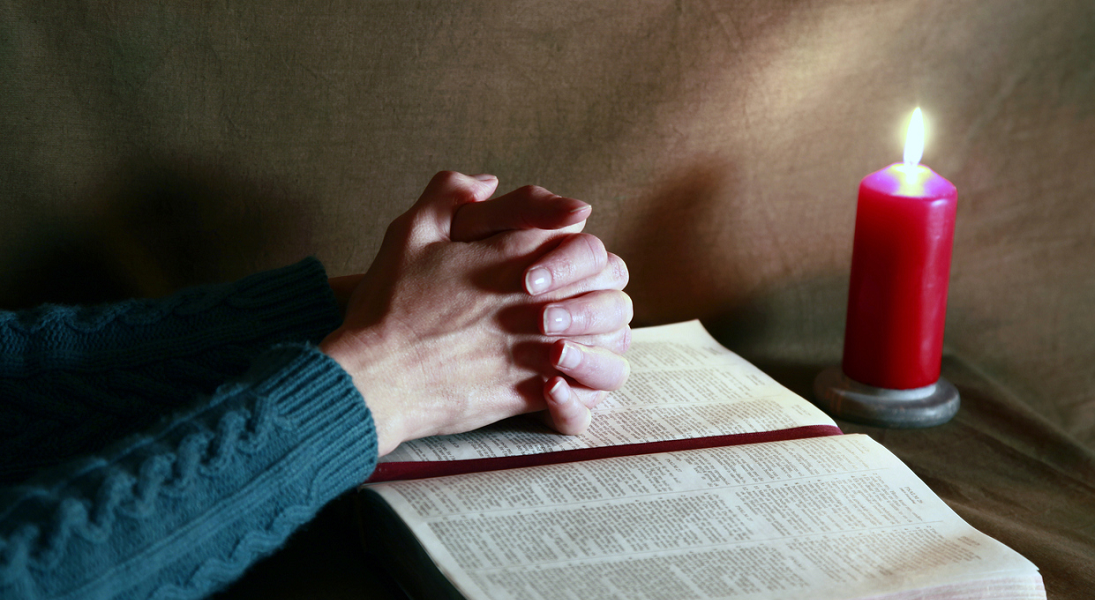 A woman's hands are folded in prayer on an open Bible beside a burning red candle