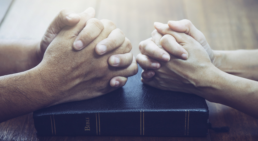 A closeup of two hands folded in prayer.