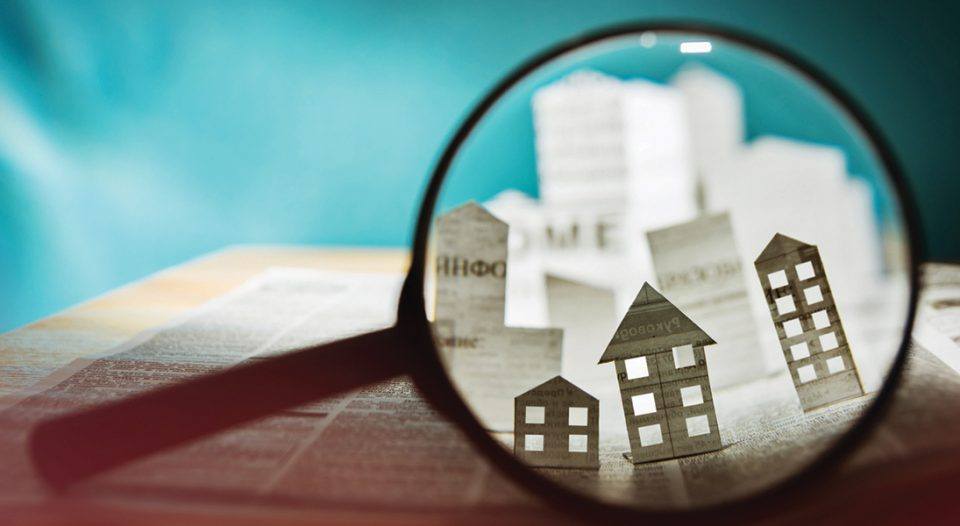 Magnifying glass in front of an open newspaper with paper houses.