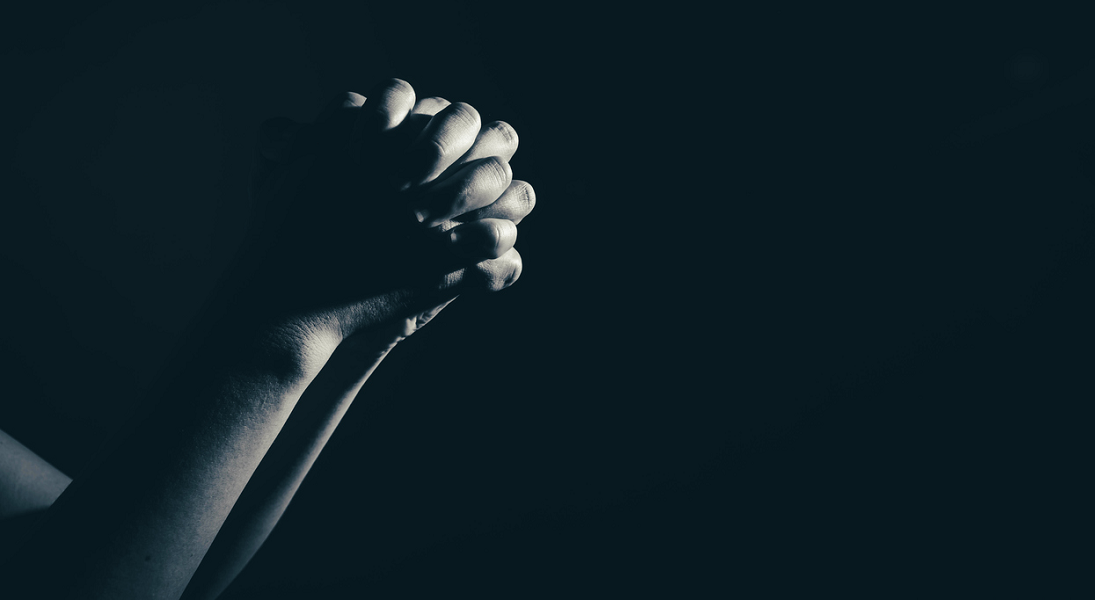 Hnds folded in prayer with a black background.
