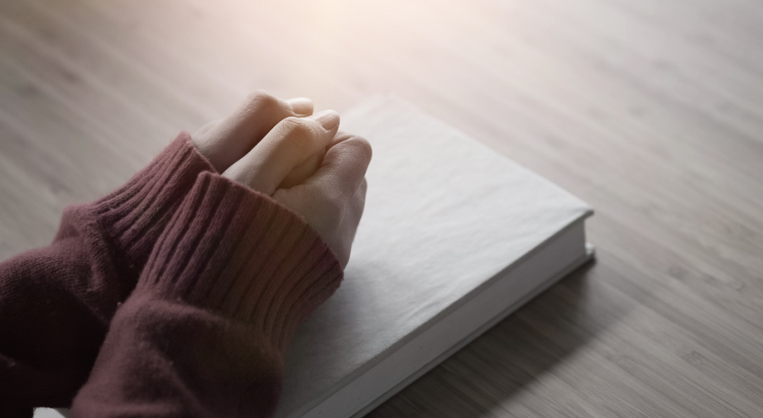 Two hands together on a closed Bible on a tabletop.