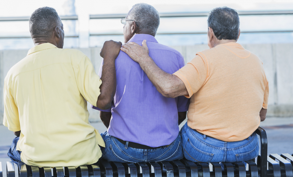 Three men on a bench with their backs to us and the center one is comforted by the other tow who each have a hand on his shoulder.