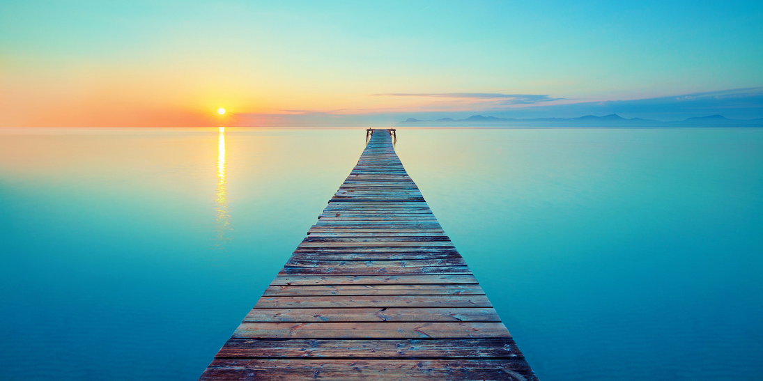 A sunrise if viewed from a dock that extends to the horizon over blue water