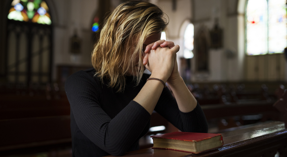 A woman prays in a church.