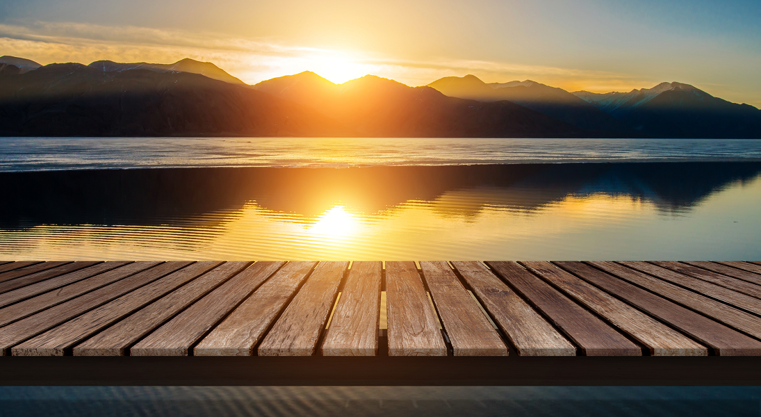 The sun rises over mountains reflected in a lake with a wooden dock in the foreground.