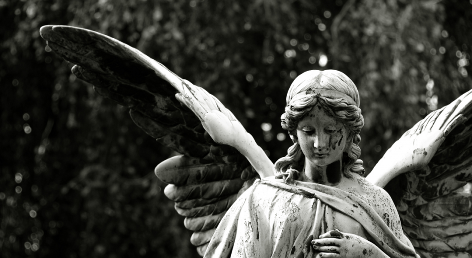 A black and white photo of a statue of an angel.