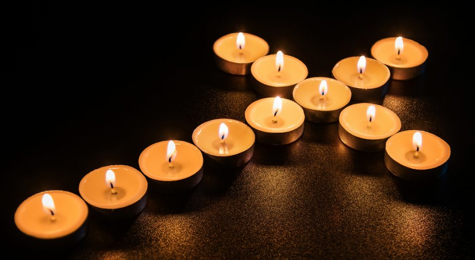 Candle in shape of cross on dark background