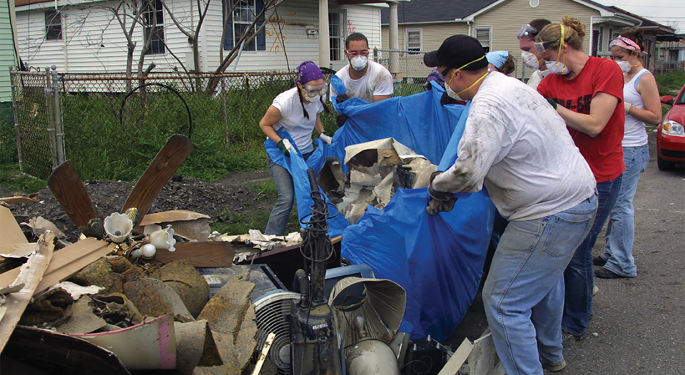 Volunteers remove debris from an abandoned house in the Lower Ninth Ward of New Orleans following the destruction done by Hurricane Katrina.