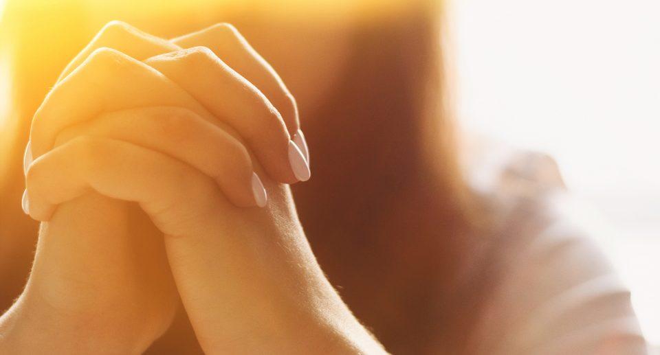 Girl folds her hands in prayer.